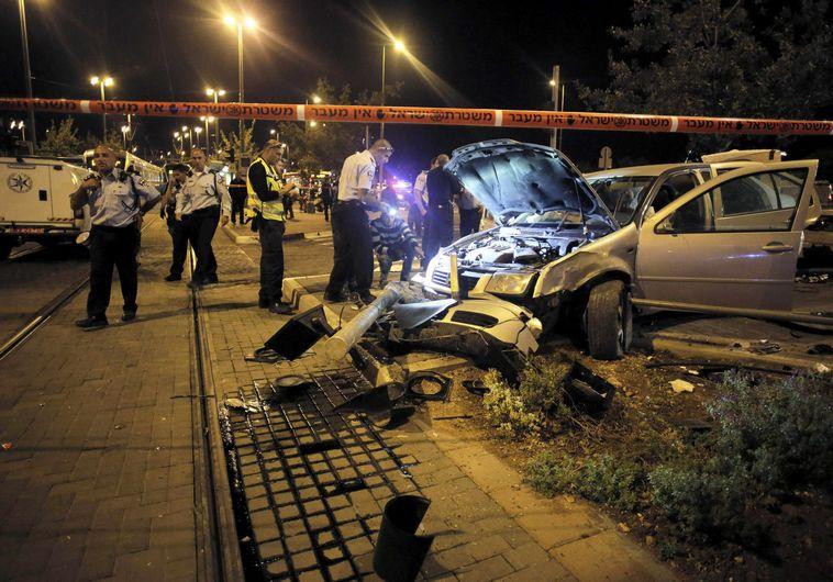 Israeli policemen inspect a car wreck in Jerusalem