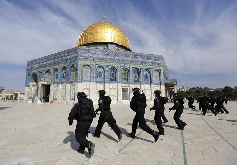 Israeli policemen run in front of the Dome of the Rock during clashes with stone-throwing Palestinians after Friday prayers in Jerusalem's Old City