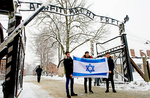 Adolescentes muestran una bandera israelí en la entrada del campo de exterminio, a modo de homenaje.