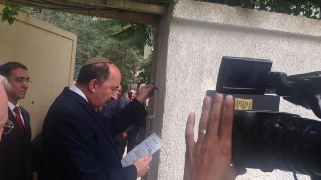 El Director de Asuntos exteriores Dore Gold coloca una Mezuzá durante la ceremonia de reapertura de la Embajada